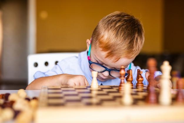 Niño con síndrome de down con gafas grandes jugando al ajedrez. Foto Premium