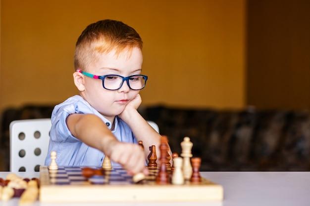 Niño con síndrome de down con gafas grandes jugando al ajedrez Foto Premium