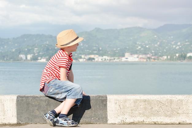 Niño con un sombrero y una camiseta a rayas sentado en la playa y mira al mar. vista lateral Foto Premium