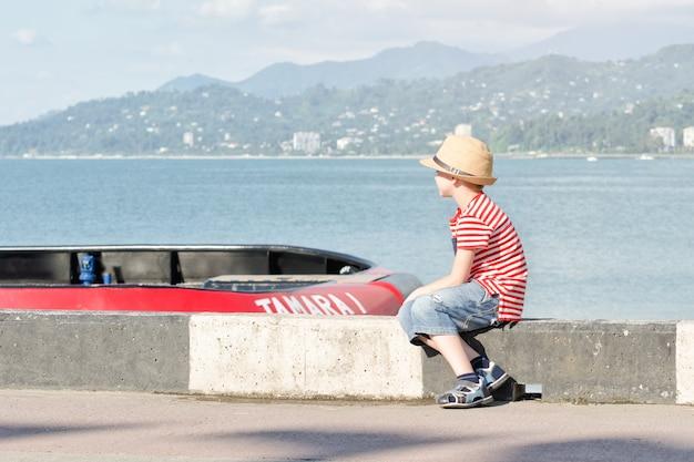 Niño con un sombrero y una camiseta a rayas sentado en la playa y mira el barco. vista lateral Foto Premium