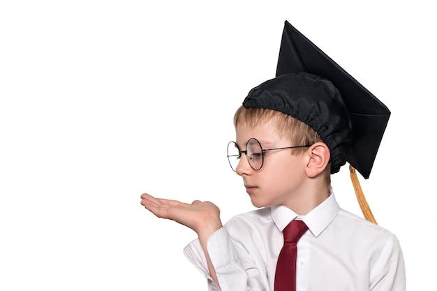 Niño con un sombrero cuadrado académico y gafas sostiene su palma hacia arriba. concepto de escuela aislar Foto Premium