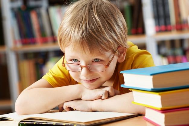 Niño sonriendo en la biblioteca Foto Gratis