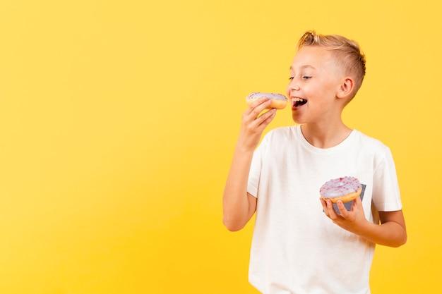 Niño sonriente comiendo deliciosas donas Foto gratis