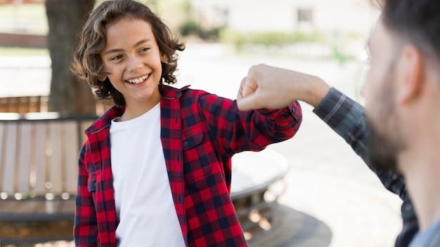 Niño sonriente golpeando el puño con su padre mientras está al aire libre Foto gratis