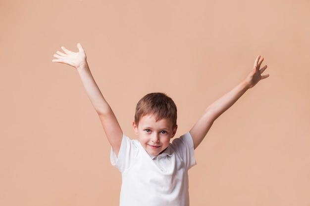 Niño sonriente inocente con la mano levantada de pie delante de fondo beige Foto gratis