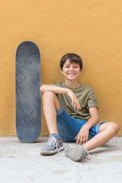 Un niño sonriente con monopatín sentado solo Foto Premium