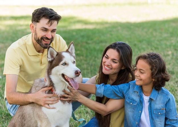 Niño sonriente y padres acariciando a un perro en el parque Foto gratis