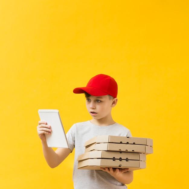 Niño sorprendido con espacio de copia de bloc de notas Foto gratis