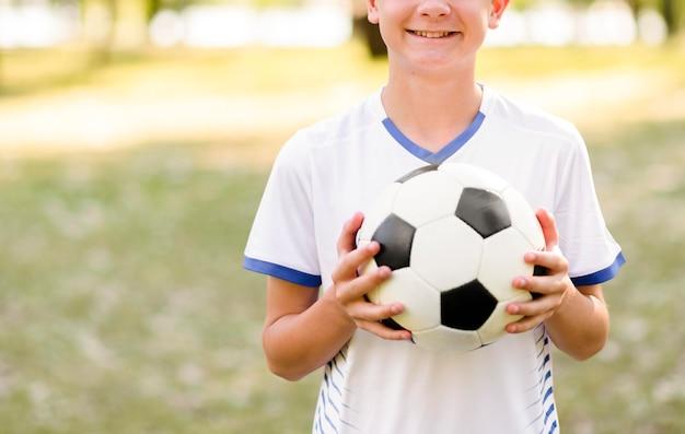 Niño sosteniendo una pelota de fútbol al aire libre con espacio de copia Foto gratis
