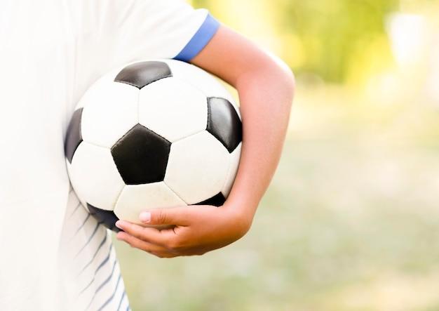 Niño sosteniendo una pelota de fútbol con primer plano de espacio de copia Foto gratis
