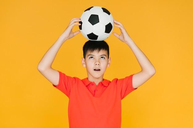 Niño sosteniendo una pelota de fútbol en su cabeza Foto gratis
