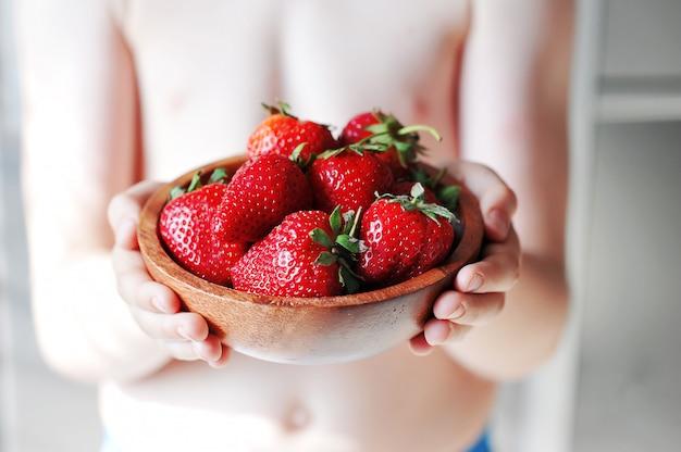 Niño está sosteniendo un plato con fresa roja fresca Foto Premium