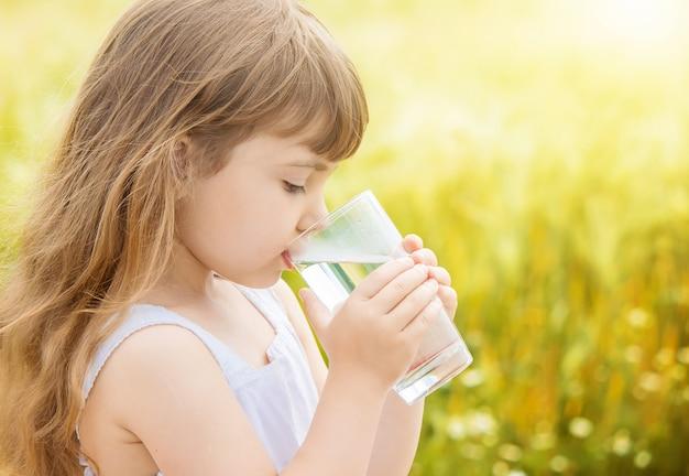 El niño sostiene un vaso de agua en sus manos. enfoque selectivo Foto Premium