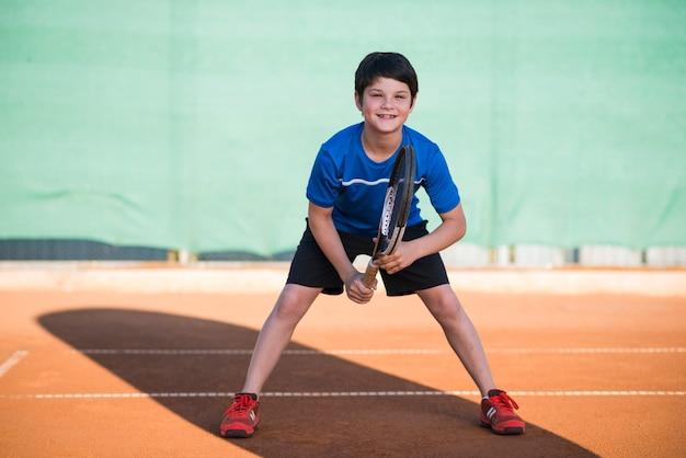 Niño tiro largo jugando tenis Foto Premium
