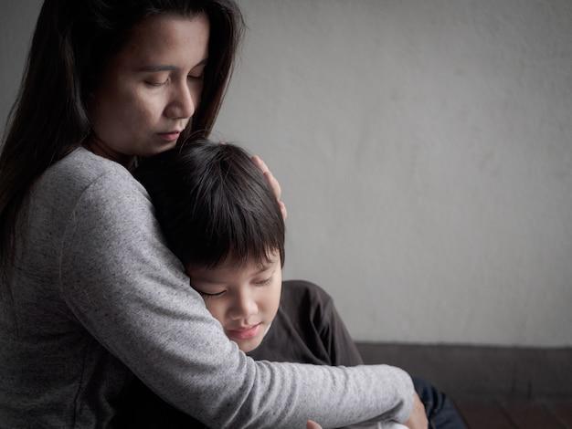 Niño triste que es abrazado por su madre en casa. paternidad, concepto de amor. Foto Premium