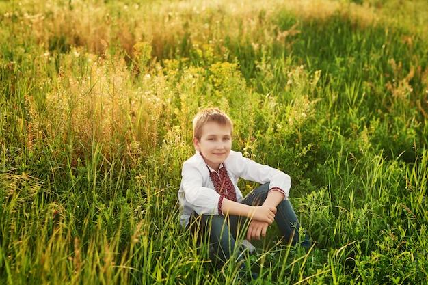 Niño ucraniano niño en bordado en el campo Foto Premium