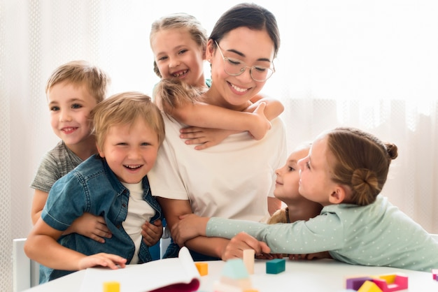 Niños abrazando a su maestra Foto Premium