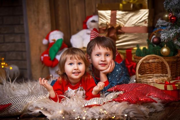 Niños acostados en la piel con un gorro de papá noel junto al árbol de navidad Foto Premium