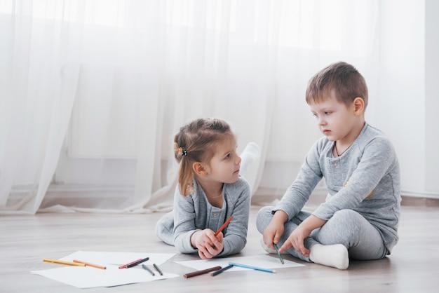 Los niños se acuestan en el piso en pijama y dibujan con lápices. lindo niño pintando con lapices Foto Premium