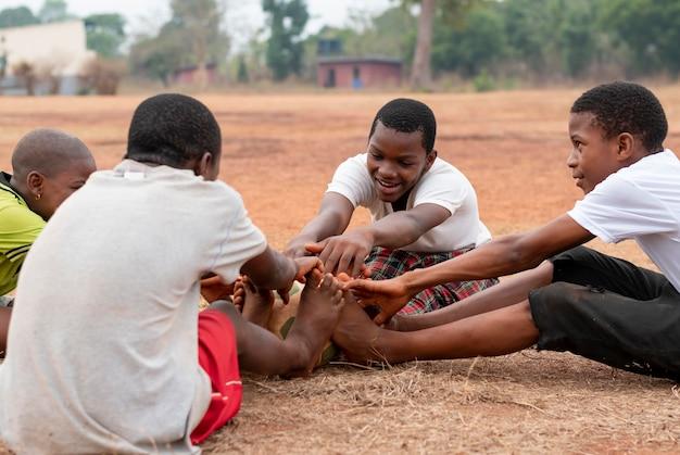 Niños africanos con pelota de fútbol sentado Foto gratis