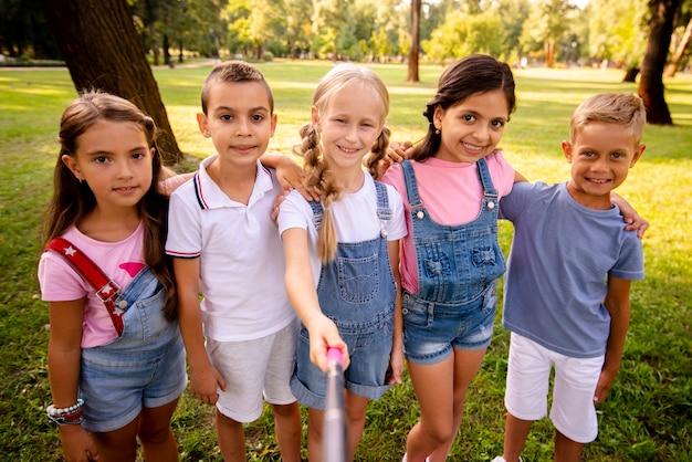Niños alegres tomando una selfie en el parque Foto gratis