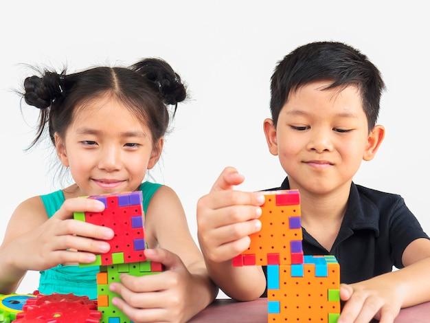 Niños asiáticos están jugando rompecabezas creativo juego de bloques de plástico Foto gratis