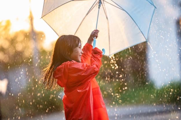 Niños asiáticos extendiendo paraguas jugando bajo la lluvia, ella lleva ropa impermeable. Foto gratis