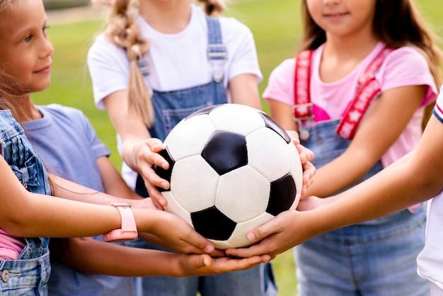 Niños con balón de fútbol en las manos Foto gratis