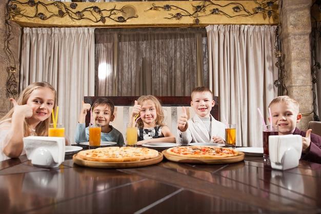 Los niños comen pizza en un restaurante. Foto Premium