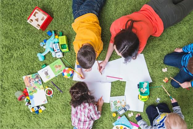 Niños dibujando y jugando en la alfombra Foto gratis
