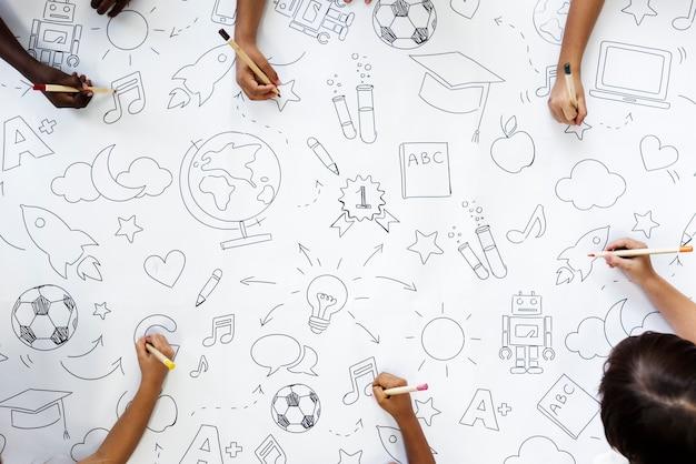 Niños dibujando símbolos de educación | Descargar Fotos premium