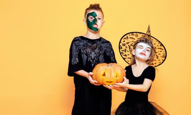 Niños en disfraces de halloween jugando con calabaza Foto Premium
