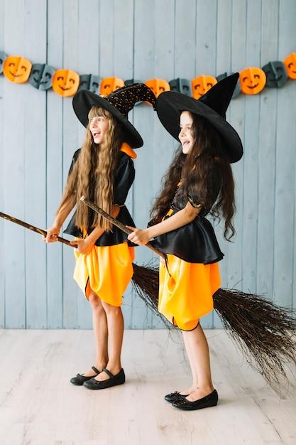 Niños disfrazados de brujas sosteniendo palos de escoba entre las piernas - Foto Gratis