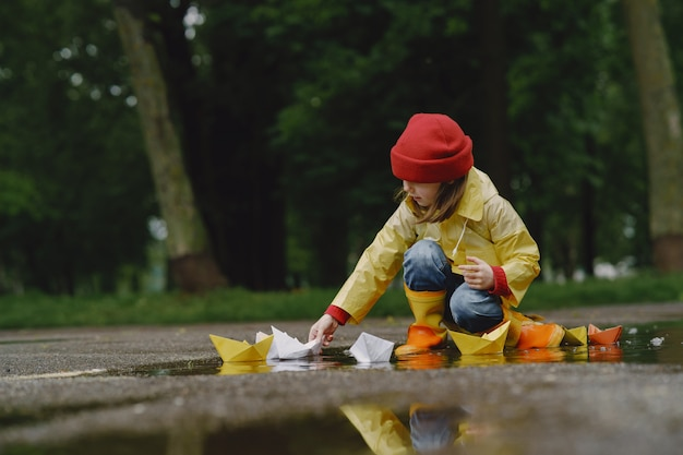 Niños divertidos en botas de lluvia jugando con barco de papel por un charco Foto gratis
