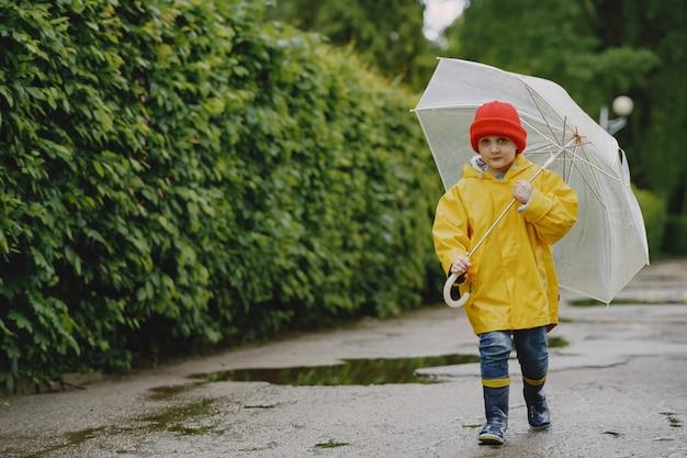 Niños divertidos en botas de lluvia jugando junto a un charco Foto gratis