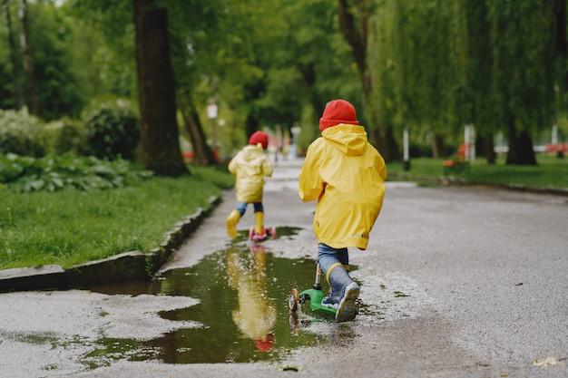 Niños divertidos con botas de lluvia jugando con patines Foto gratis
