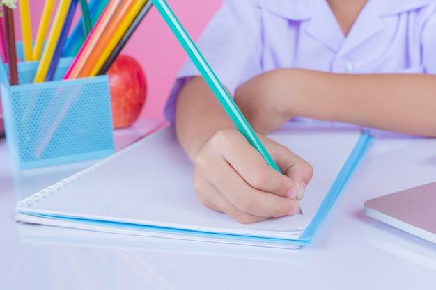 Los niños escriben gestos de libros sobre un fondo rosa. Foto gratis