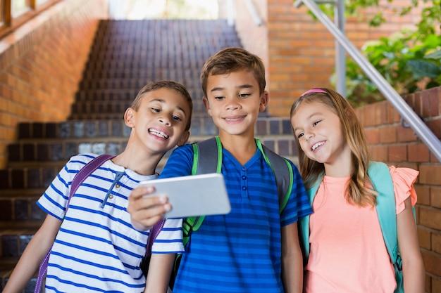 Niños de la escuela tomando selfie desde teléfono móvil Foto Premium