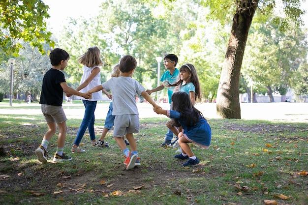 Niños felices jugando juntos al aire libre, bailando sobre el césped, disfrutando de actividades al aire libre y divirtiéndose en el parque. concepto de fiesta o amistad para niños Foto gratis