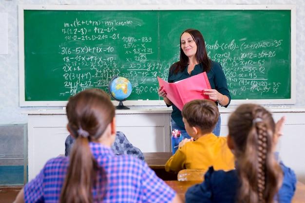 Los niños hacen matemáticas en la escuela primaria. Foto Premium