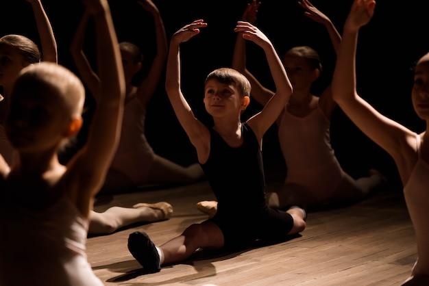 Niños haciendo divisiones mientras se calientan en el escenario Foto Premium