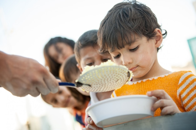 Niños hambrientos siendo alimentados por caridad Foto Premium