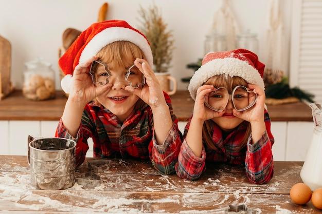 Niños jugando con forma de galletas lindas Foto gratis