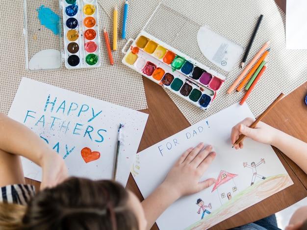 Niños laicos planos dibujando para el día del padre Foto gratis