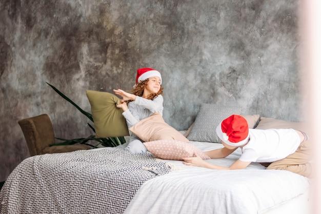 Niños lindos entre adolescentes con sombreros de santa y pijama jugando en la cama con la almohada, la mañana de navidad, fiesta infantil Foto Premium