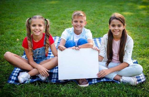 Niños en manta sosteniendo un cartel en las manos Foto gratis