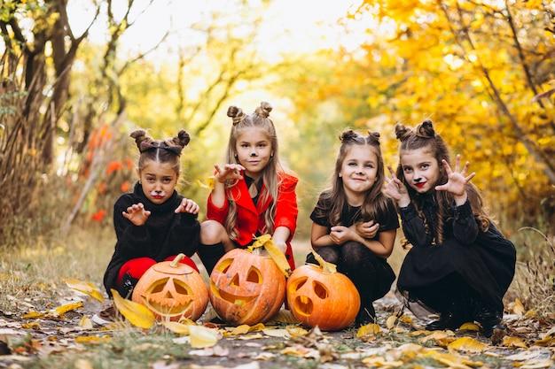Niños niñas vestidas con disfraces de halloween al aire libre con calabazas Foto gratis