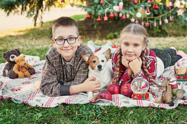 Niños niño y niña con un perro jack russell terrier cerca de un árbol de navidad con regalos, Foto Premium