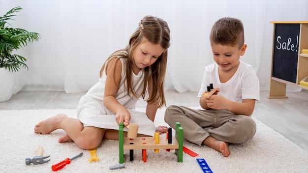 Niños no binarios jugando con juego colorido. Foto gratis