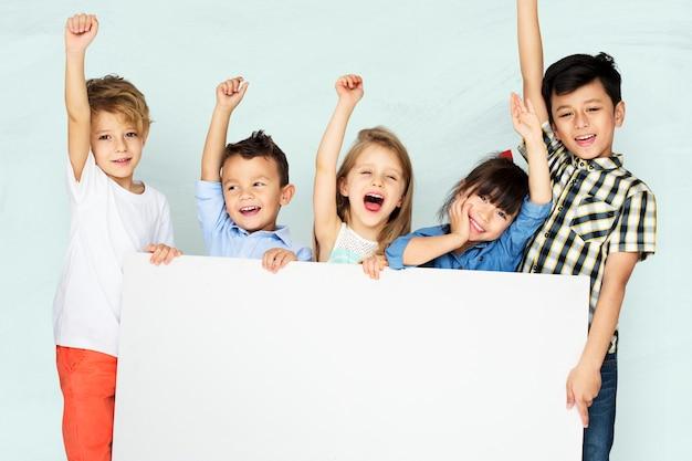 Niños pequeños animando mientras sostiene una pizarra blanca Foto gratis